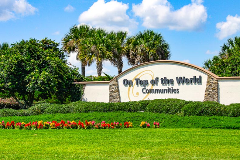 Greenery surrounding the community sign for On Top of the World in Ocala, Florida