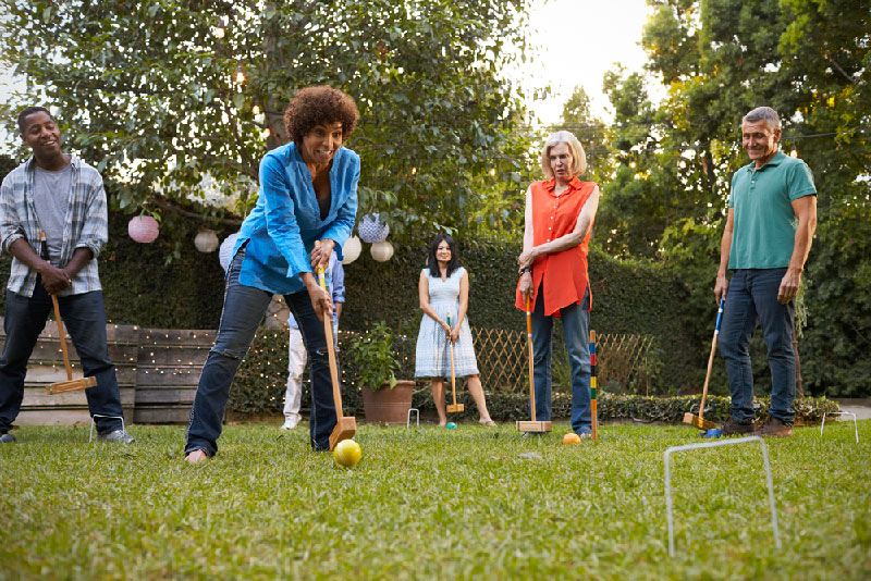 group of mature friends playing croquet in backyard