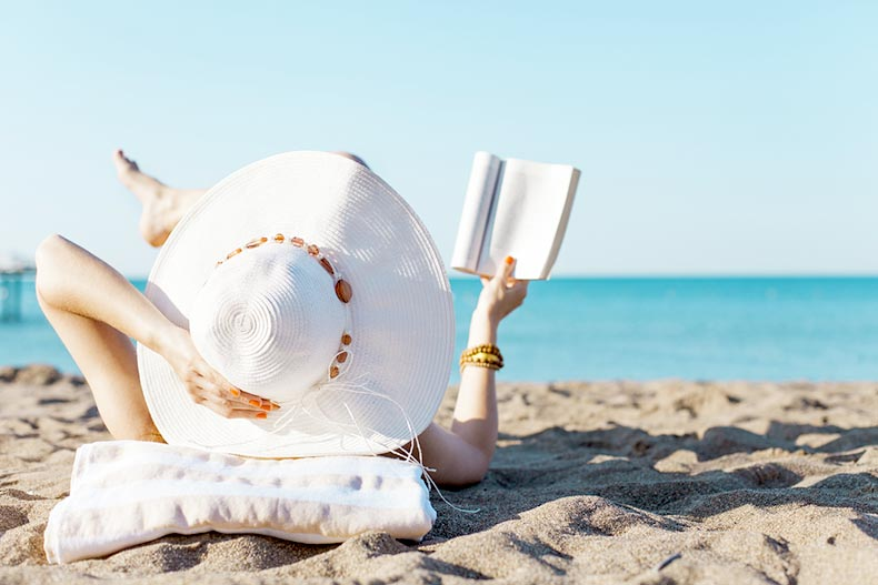 Woman in a hat reading a book on a beach