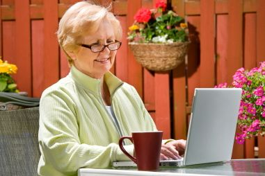Smiling woman sitting at desk with laptop