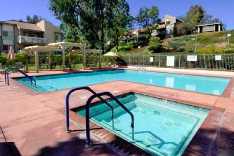 Outdoor amenities include a sparkling outdoor pool, spa, and patio.