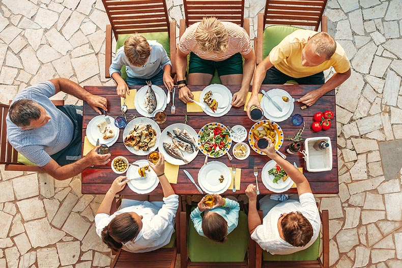 A top-down view of a multigenerational family enjoying a meal together outdoors