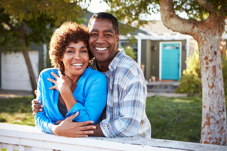 mature couple standing in front of new home smiling
