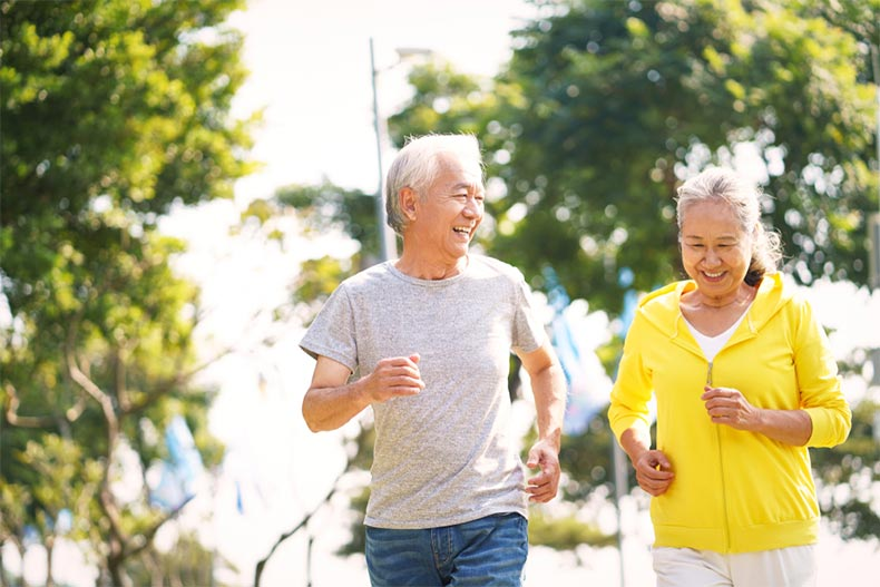 A senior couple smiling while jogging together on a sunny day