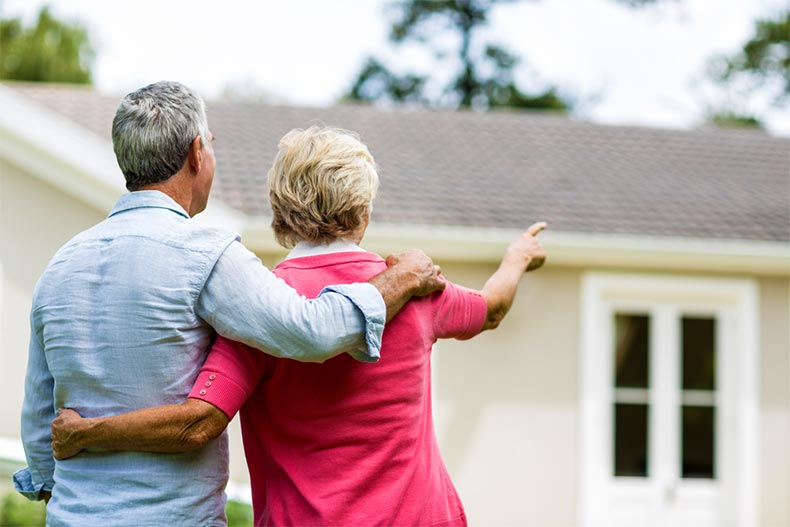 Active adult couple looking at house while standing in the yard