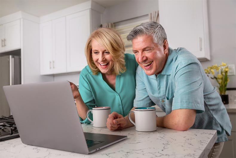 Active adult couple smiling while video chatting in the kitchen