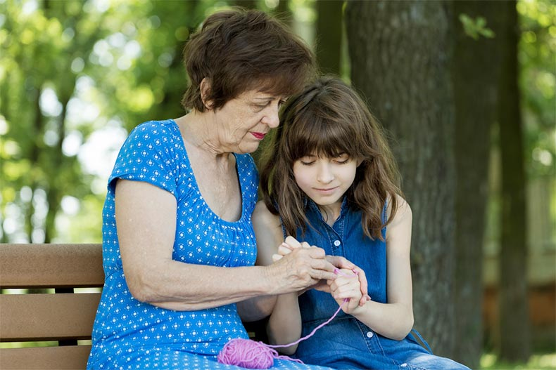 A grandmother teaching her granddaughter to crochet while sitting on a park bench in the summer