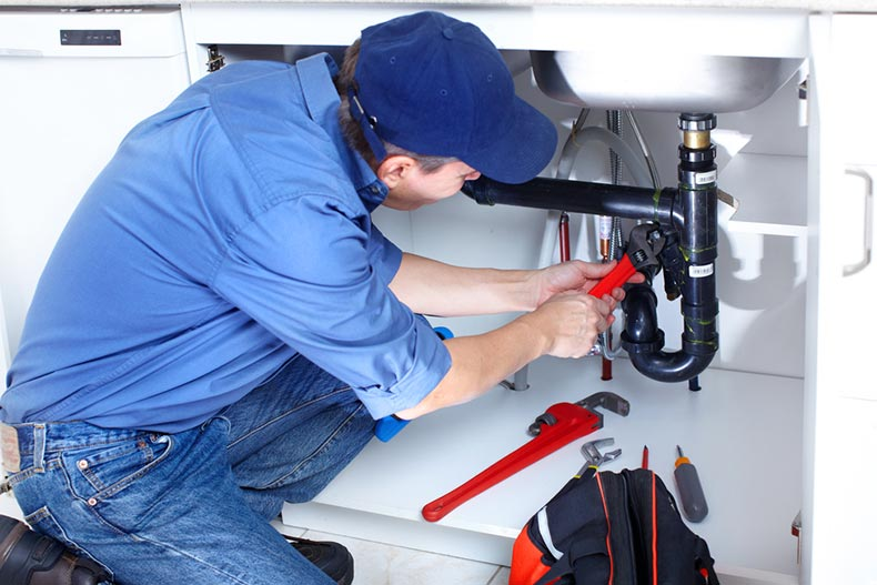 A plumber fixing a sink before a homebuyer closes on the home sale