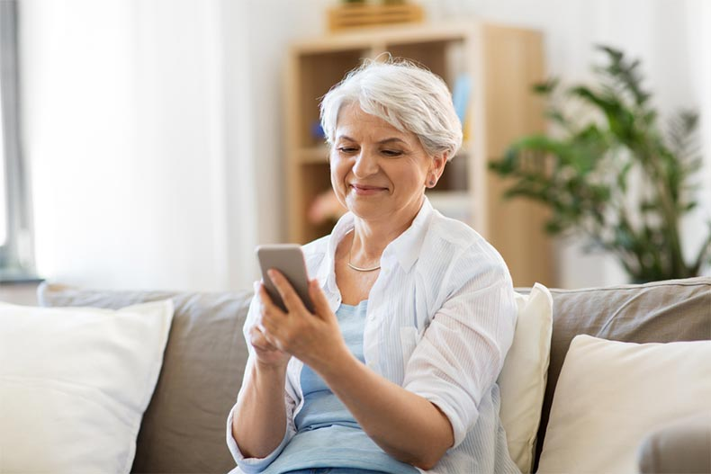 A senior woman sitting on a couch and downloading a retirement app on her smartphone