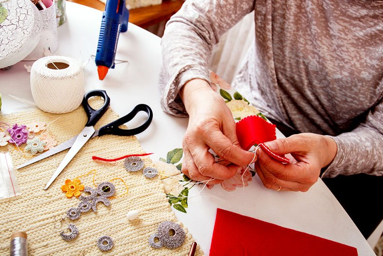 A woman sews a decoration in an arts studio.