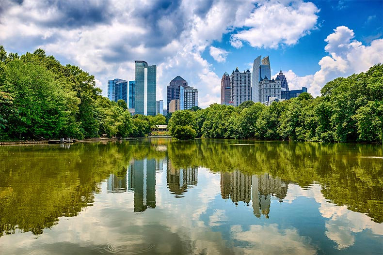 Pond surrounded by trees with downtown Atlanta skyline in the background