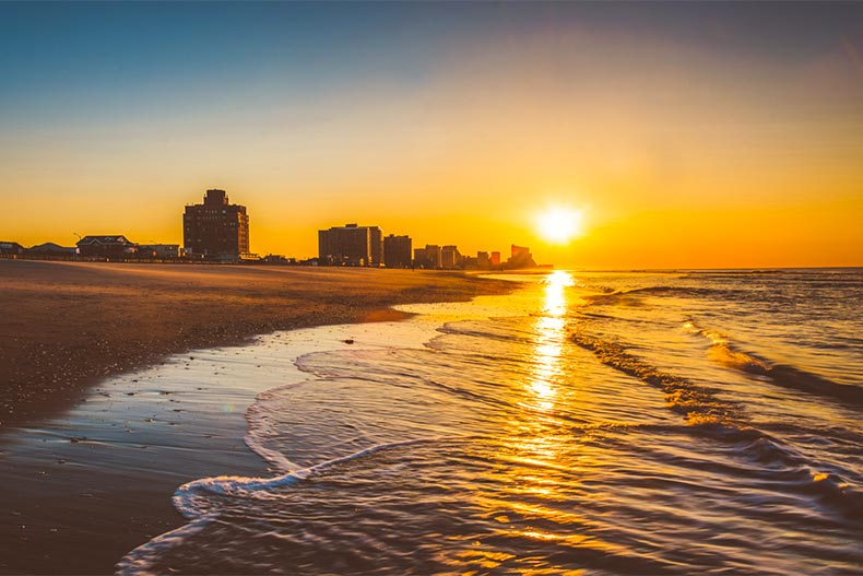 Sunrise over the water and beach of Atlantic City with skyline in the background
