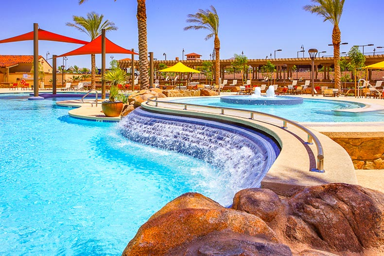 View of palm trees around the outdoor pool and patio at Sun City Festival in Buckeye, Arizona