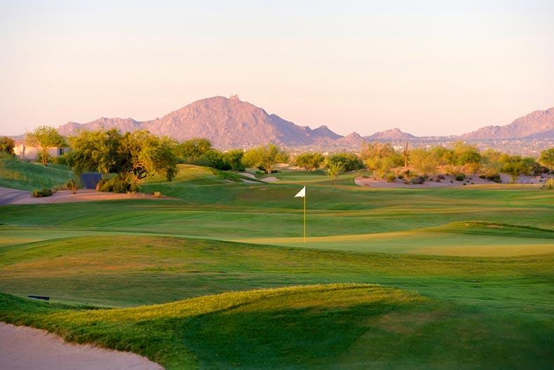 Sunset view of a golf course in the Arizona desert with mountains in the background