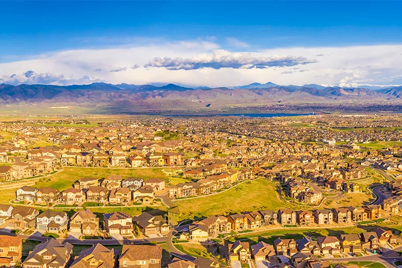 Aerial view of homes with Rocky Mountains behind them in the large BackCountry community