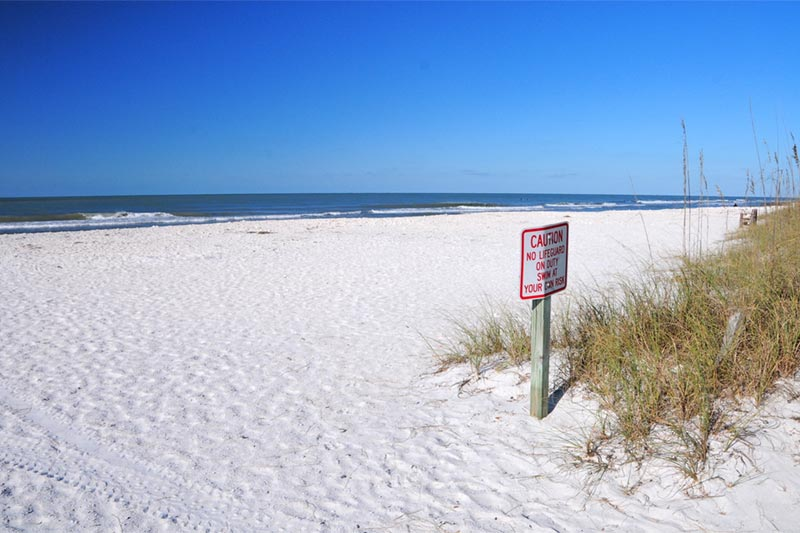 empty beach with white sand and waves with caution sign.