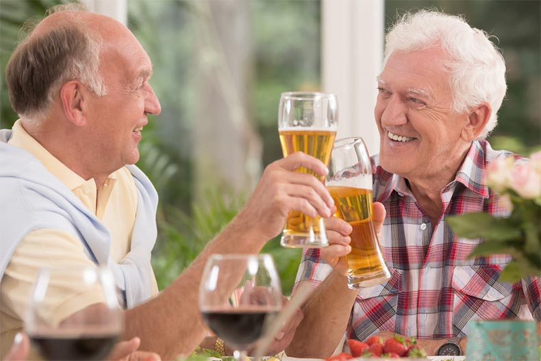 Two older men smiling while drinking beer at an outdoor table
