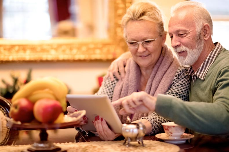 An active adult couple using a tablet to shop online for a home in a 55+ community