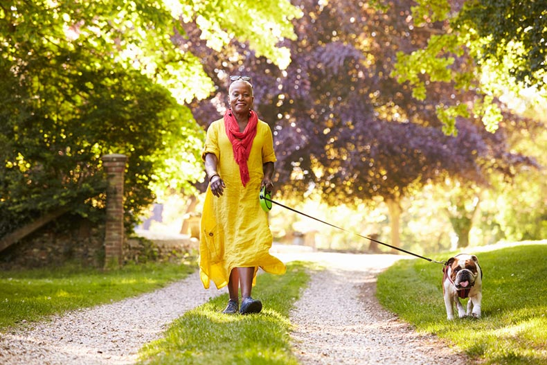 A senior woman in a dress walking her dog along a trail on a summer day
