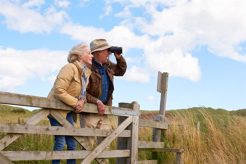 A senior couple standing by a fence and bird watching