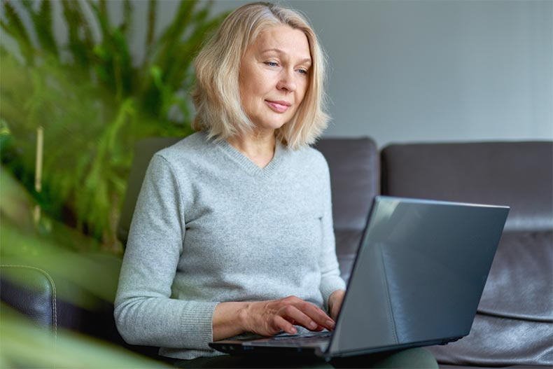 An older woman sitting on a couch while working on her blog