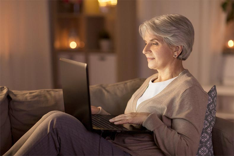 A senior woman at home in the evening and blogging on her laptop