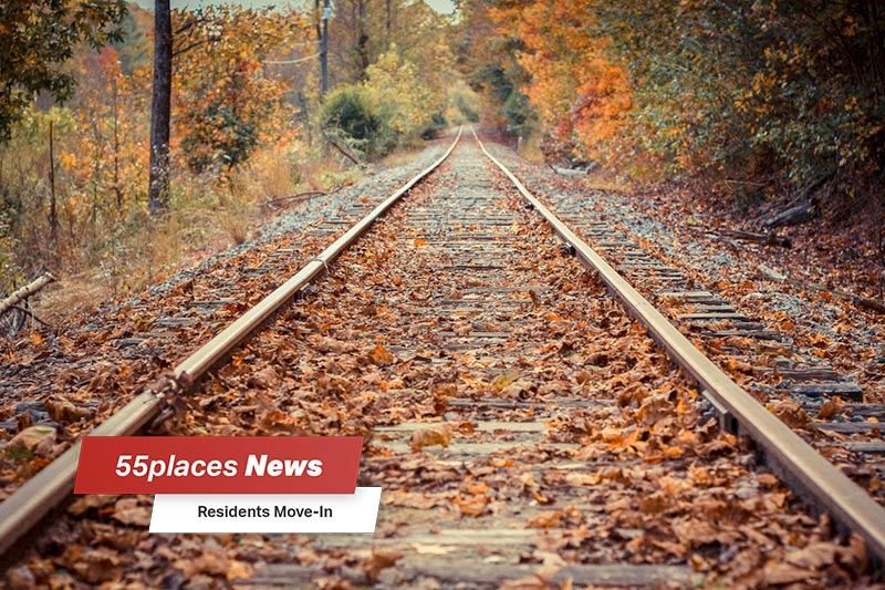 """55places News: Residents Move-In"" banner over railroad tracks through the autumn woods in Blue Ridge, Georgia"