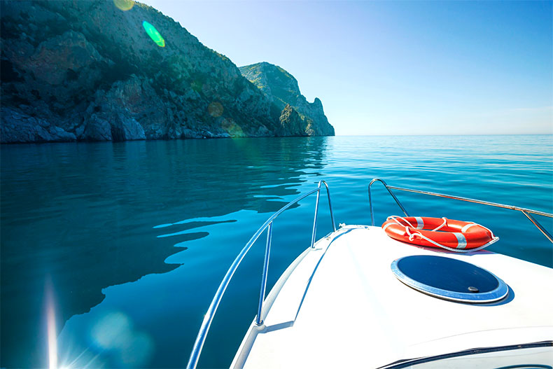 View of the front of a boat in the water surrounded by cliffs.