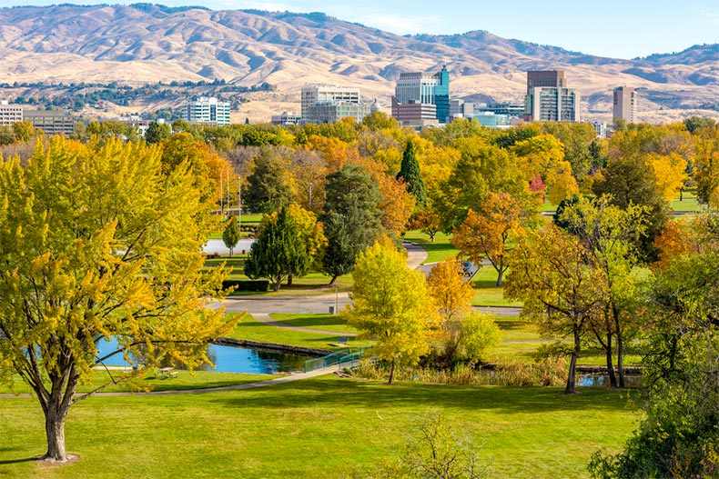 Closeup of a park with autumn colors and Boise, ID skyline and mountains behind it.