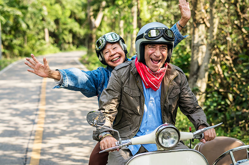 Senior couple happily driving along shaded road on motorcycle.