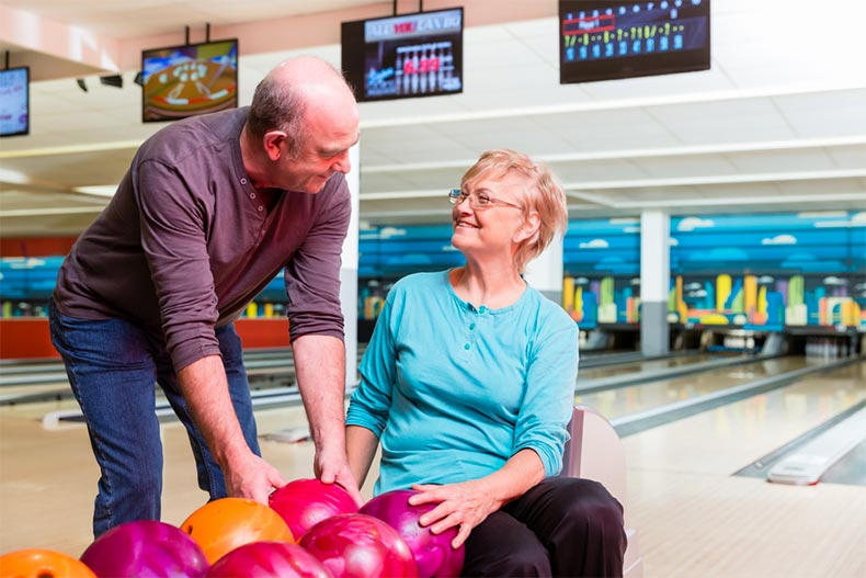 Older couple choosing balls at a bowling alley