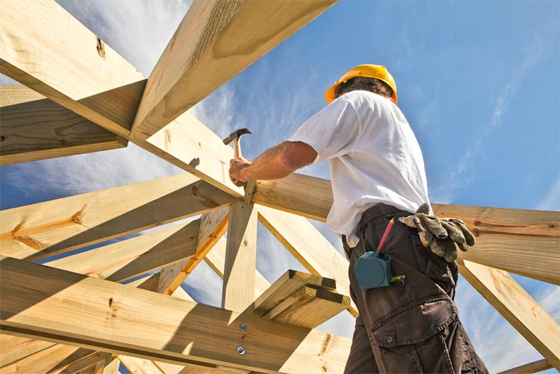 A carpenter working on a roof structure at a construction site