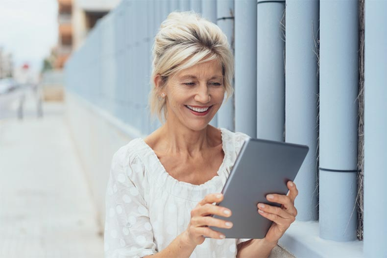 An older woman walking down a street and smiling while using a tablet
