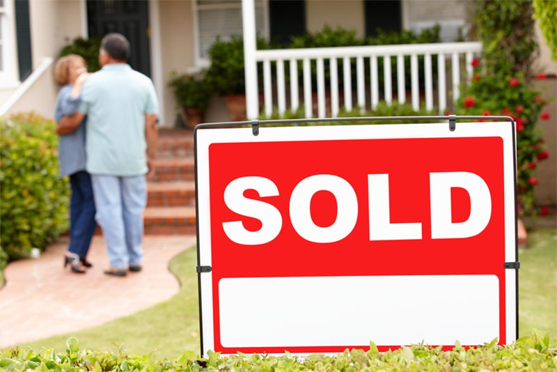 sold sign in front of couple buying home