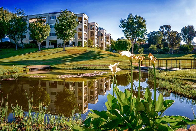 View across a picturesque pond of condo buildings at Laguna Woods Village in Laguna Woods, California