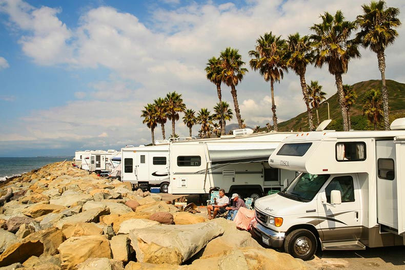 Two active adults sitting beside a line of RVs on the rocky beaches of Faria Beach National Park in Venture, California