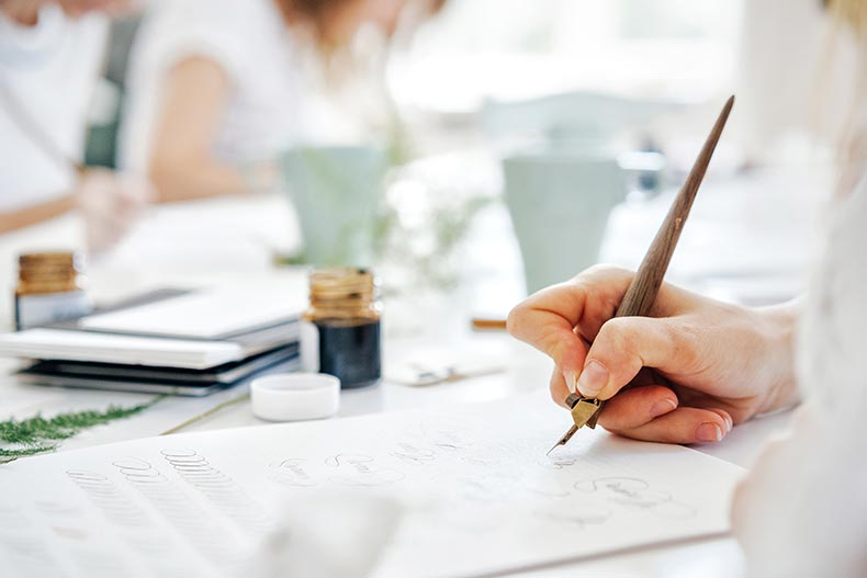 Closeup on a woman's hand using a pen as she learns calligraphy in a class