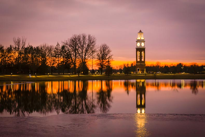 The bell tower along the lake at Coxhall Garden in Carmel, Indiana at sunset