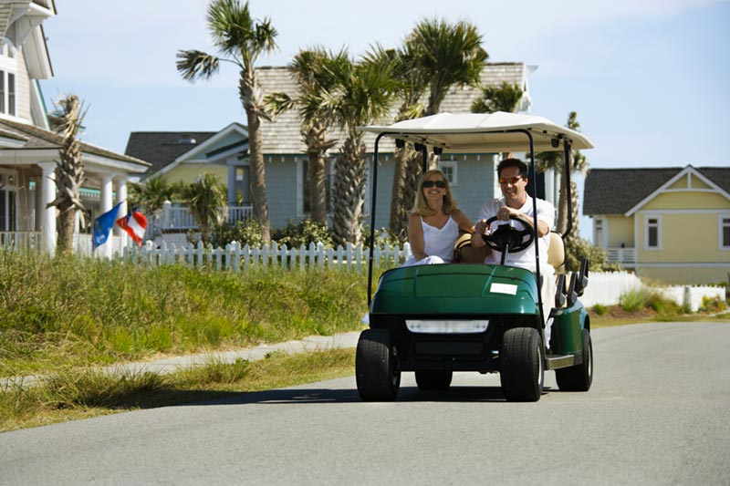 couple driving a golf cart in residential community on street