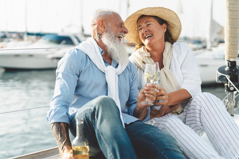 A senior couple toasting champagne on a sailboat to celebrate their retirement