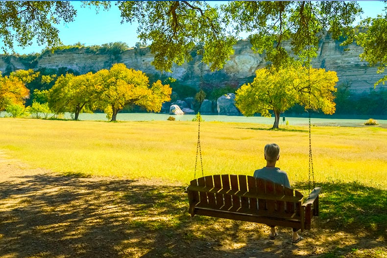 Man sitting on a bench swing looking out over a field in Central Texas