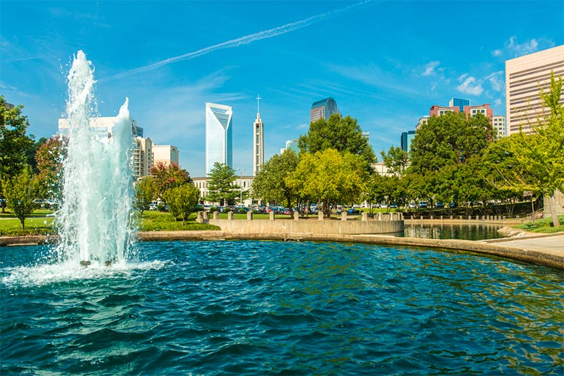 Fountain in Marshall Park with Charlotte skyline peaking through trees.