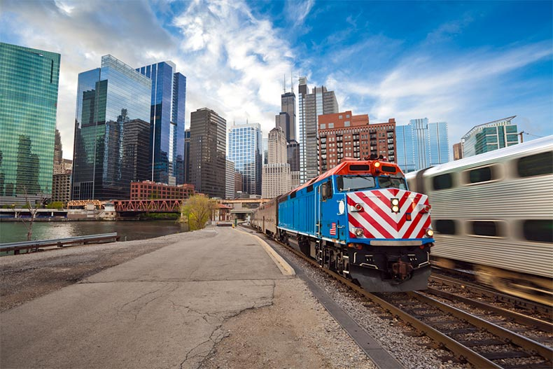 Metra train on tracks while another train heads the other way into Chicago and its skyline