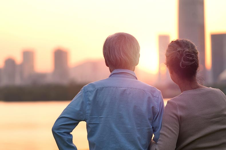 Rear view of a senior couple by a river looking at the sunset over a city skyline