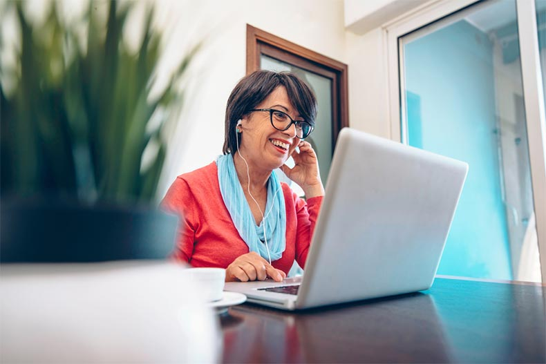 An older woman with earbuds in smiling while taking an online class