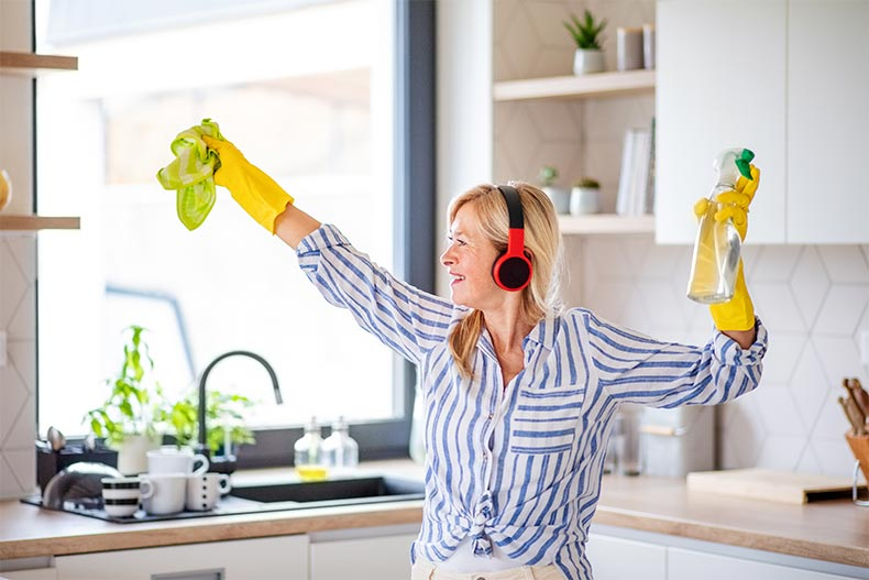 A senior woman with headphones and gloves cleaning in her kitchen