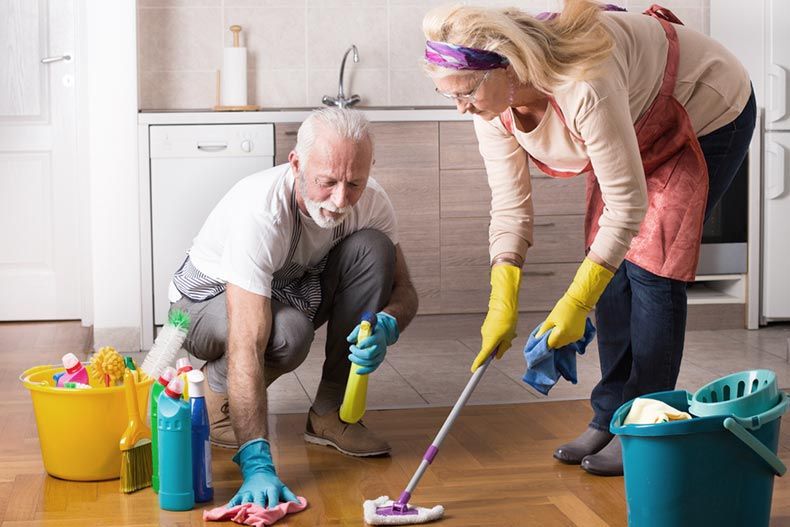 A senior couple working together to clean the kitchen floor