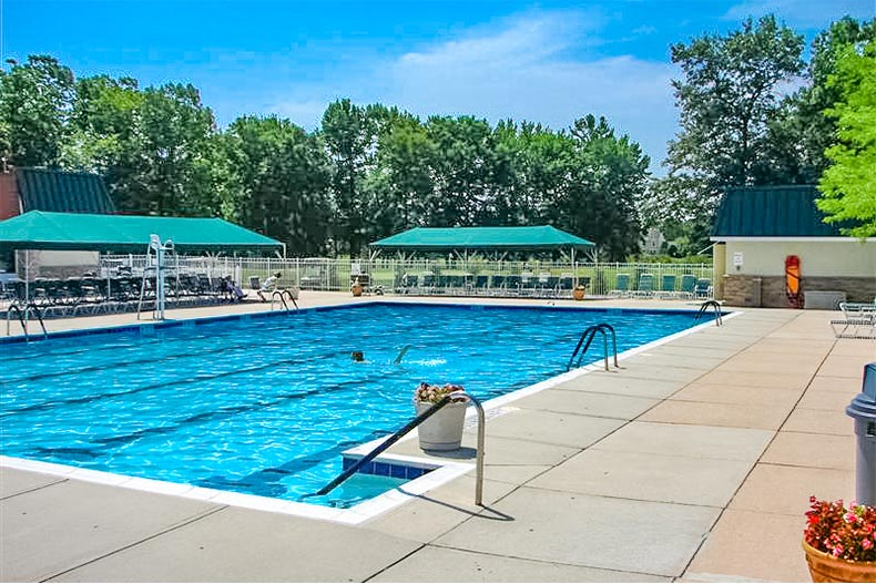 Outdoor lap pool with shaded chairs in Clearbrook