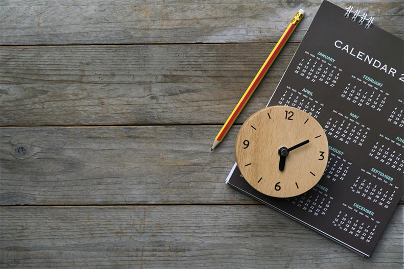 Close up of a clock, calendar, and pencil on a table