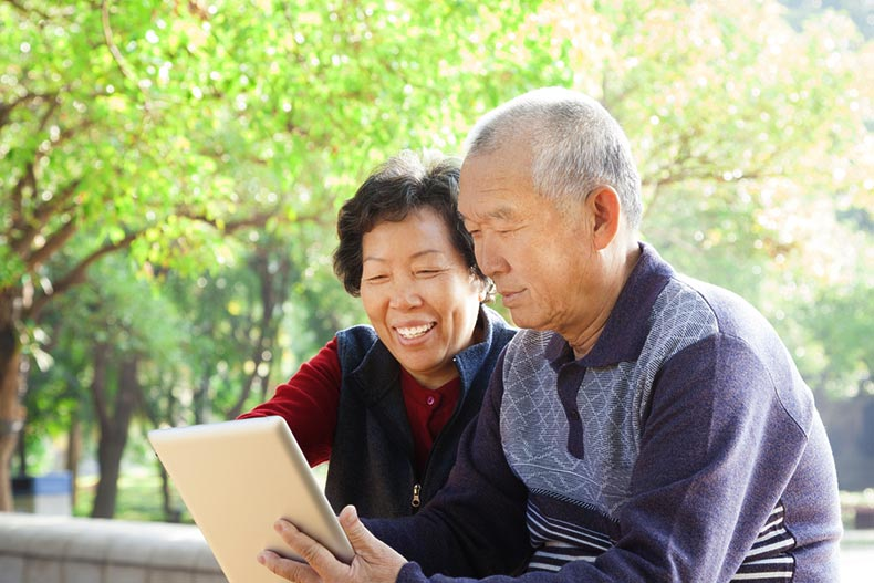 An active adult couple in a park signing their closing documents on a tablet